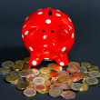 Euro coins with red saving pig on black background — Stock Photo