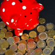 Red saving pig with coins — Stockfoto