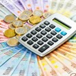 Calculator on euro coins and banknotes background — Stock Photo