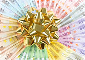 Money as a gift. golden ribbon on euro banknotes — Foto Stock