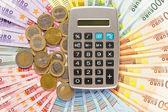 Rechner auf euro-münzen und banknoten-hintergrund — Stockfoto