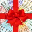 Red gift ribbon bow over euro banknotes — Stock Photo #14229043