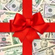 Red gift ribbon bow over american dollars — Stock Photo