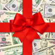 Red gift ribbon bow over american dollars — Stock Photo #14229081