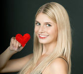 Beautiful young blond girl with red heart — Stock Photo