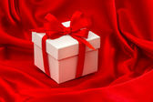 White gift box with bow over red satin — Stock Photo