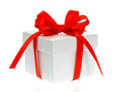 White gift box with red bow ribbon — Stock Photo