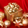 Gift box with golden christmas balls on red silk — Stock Photo #14565235