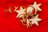 Golden christmas balls over red silk background — Stock Photo