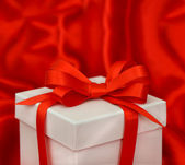 White gift box with red bow ribbon — Stockfoto