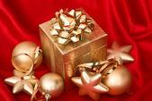 Dárková krabička s zlatý vánoční koule červené hedvábí — Stock fotografie