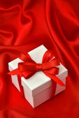 White gift box with red ribbon over silk — 图库照片