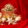 Stock Photo: Golden christmas balls over red silk
