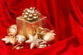 Goldene weihnachtskugel in roter seide — Stockfoto