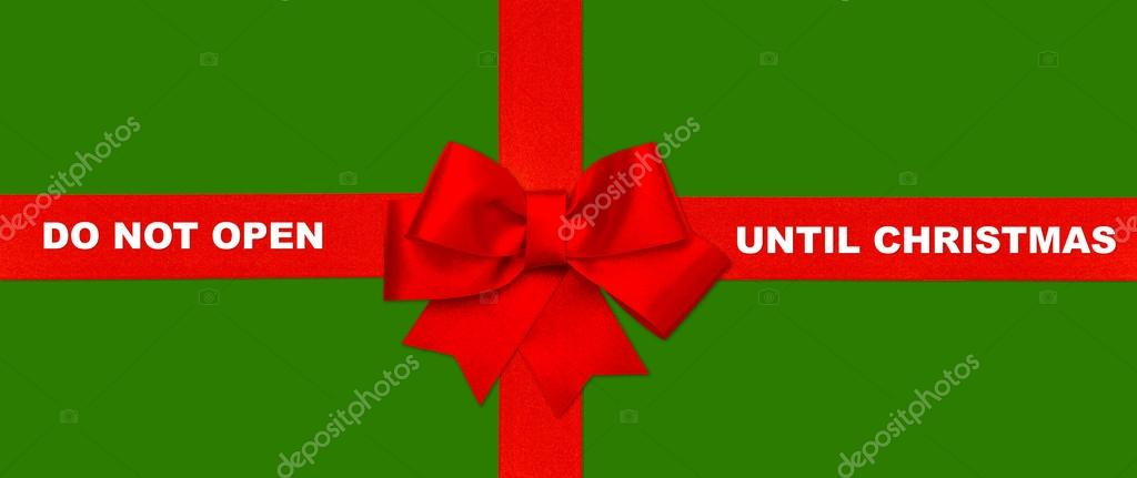 Red ribbon bow on green gift background with text DO NOT OPEN UNTIL CHRISTMAS — Stock Photo #14715149