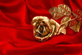 Golden rose over red satin background — Stok fotoğraf