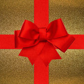 Red ribbon bow over golden background — Stock Photo