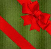 Fiocco di nastro rosso sopra verde cartone riciclato — Foto Stock