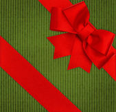 Red ribbon bow over green recycled cardboard — Stock Photo