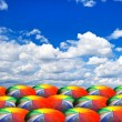 Rainbow umbrellas on beautiful cloudy sky — Stock Photo