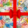 Euro currency banknotes with red gift ribbon — Stock Photo