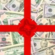 Red gift ribbon with bow over american dollars — Stock Photo