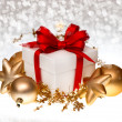 White gift box with red ribbon and golden balls — Stock Photo