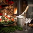 Bottle of champagne, glasses and fireplace - Stock Photo