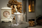 Home interior wirh champagne, vintage clock and fireplace — Stock Photo