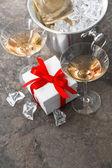 Dwie szklanki, butelkę szampana i dar — Zdjęcie stockowe