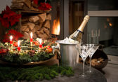 Bottle of champagne, glasses and fireplace — Stock Photo