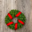 Royalty-Free Stock Photo: Christmas wreath with red ribbon on wooden background