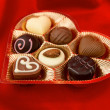 Stock Photo: Chocolate pralines in golden box on red satin