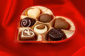 Chocolate pralines in golden box on red satin — Stock Photo