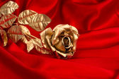 Golden rose over red silk background — Стоковое фото