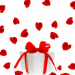 Stock Photo: Gift box with red ribbon bow and rose flower petals