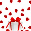 Gift box with red ribbon bow and rose flower petals — Stock Photo