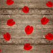 Red rose petals on wooden background — Stock Photo