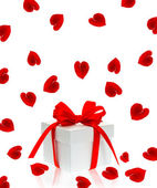 Gift box with red ribbon bow and rose flower petals — Stok fotoğraf