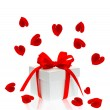 Gift box with red ribbon bow and rose flower petals - Foto Stock