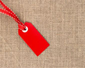 Red label with ribbon on burlap — Stock Photo