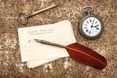 Old post cards, clock, key and feather pen — Stock Photo