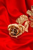 滑らかな赤のサテンの上の黄金のバラの花 — ストック写真