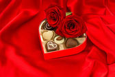 Red roses and delicious chocolate pralines — Stock Photo
