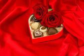 červené růže a lahodné čokoládové pralinky — Stock fotografie