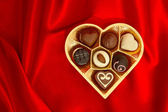 Chocolate pralines in golden heart shape gift box — Stock Photo