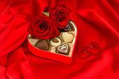κόκκινα τριαντάφυλλα με καρδιά πέταλα και σοκολάτα πραλίνες — Φωτογραφία Αρχείου