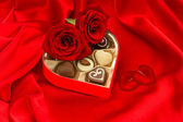 красных роз сердце лепестками и шоколадные конфеты — Стоковое фото