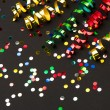 Colorful streamer and confetti on black paper background - Stock Photo