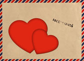 Vintage airmail envelope with red love hearts — Stock Photo